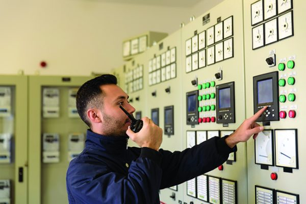 Man in front of control panel
